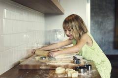 Att le för liten flicka bakar kakabegrepp royaltyfri bild