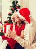Att le fadern förvånar dottern med gåvaasken Arkivbilder