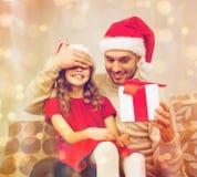 Att le fadern förvånar dottern med gåvaasken royaltyfri fotografi
