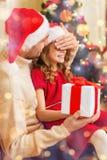 Att le fadern förvånar dottern med gåvaasken Arkivbild