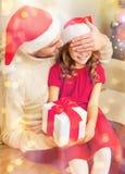 Att le fadern förvånar dottern med gåvaasken Arkivfoto