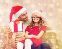 Att le fadern förvånar dottern med gåvaasken Royaltyfri Bild