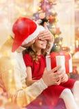 Att le fadern förvånar dottern med gåvaasken Royaltyfria Bilder