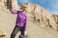 Att le flickahandelsresanden i en gul hatt och ett par av solglasögonställningar på foten av epos vaggar med en nästa ryggsäck oc arkivbilder