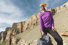 Att le flickahandelsresanden i en gul hatt och ett par av solglasögonställningar på foten av epos vaggar med en nästa ryggsäck oc royaltyfri foto