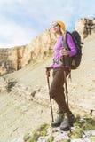 Att le flickahandelsresanden i en gul hatt och ett par av solglasögonställningar på foten av epos vaggar med en nästa ryggsäck oc fotografering för bildbyråer