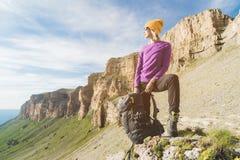 Att le flickahandelsresanden i en gul hatt och ett par av solglasögonställningar på foten av epos vaggar med en nästa ryggsäck oc royaltyfria bilder