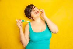 Att le flickan med kort hår och ett curvy diagram står med en tandborste i hennes händer på gul fast studiobakgrund royaltyfri fotografi