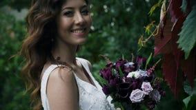 Att le flickan ser och trycker på en bukett av blommor Stående av en gullig kvinna lager videofilmer