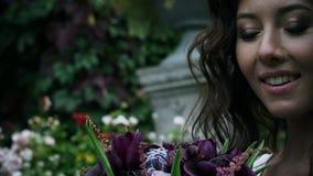 Att le flickan ser och trycker på en bukett av blommor Stående av en gullig kvinna arkivfilmer