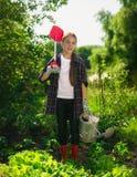 Att le flickan som poserar på trädgården med spaden och bevattnar kan Fotografering för Bildbyråer