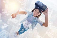 Att le flickavisning tummar upp, medan ta bort VR-hörlurar med mikrofon royaltyfri bild