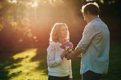 Att le kvinnahäleri blommar från hennes make utanför Arkivbild