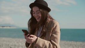 Att le kvinnan är att prata direktanslutet vid smartphonen med internet på havskust arkivfilmer