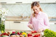 Att le kvinnan är att skiva tomater på ett köksbord Royaltyfria Bilder