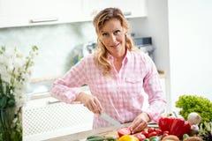 Att le kvinnan är att skiva tomater på ett köksbord Royaltyfri Fotografi
