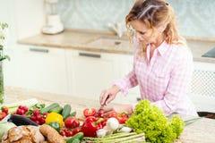 Att le kvinnan är att skiva tomater på ett köksbord Royaltyfri Foto