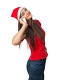 Att le kvinnan i santa hjälpredahatt talar vid telefonen Arkivfoton