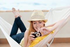 Att le kvinnan ser foto på hennes kamera i hängmatta Arkivbilder