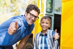 Att le lärare- och skolpojkevisning tummar upp framme av skolbussen royaltyfri bild