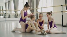 Att le lilla flickan är att fixa hennes frisyr för vän` s och talar under avbrott mellan grupper i dansstudio Barndom stock video