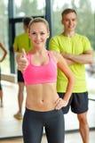 Att le man- och kvinnavisning tummar upp i idrottshall Royaltyfri Foto