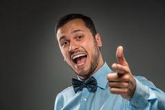 Att le mannen är att göra en gest med handen som pekar fingret på kameran Arkivfoto