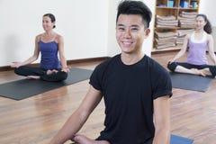 Att le mansammanträde kors-lade benen på ryggen i en yogagrupp Royaltyfri Fotografi