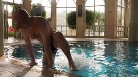 Att le manvisning tummar upp, medan simma, i att sväva pölen i brunnsorthotell stock video