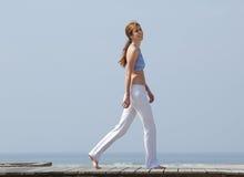 Att le mitt åldrades kvinnan som går på stranden Royaltyfria Bilder