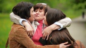 Att le modern är att krama hennes två vuxna döttrar utomhus Tre härliga kvinnor är lyckliga tillsammans lager videofilmer