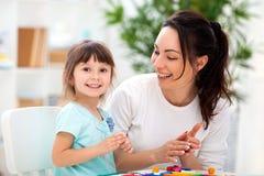 Att le modern hjälper lite dottern att hugga statyetter från plasticine Kreativitet för barn` s lycklig familj arkivfoton