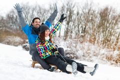 Att le och lyckliga par tycker om, i att sledding Arkivfoton