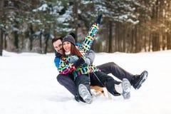 Att le och lyckliga par tycker om, i att sledding Arkivbild