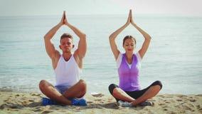 Att le praktiserande yoga för par poserar på stranden i dagen stock video