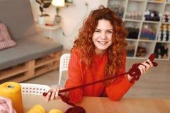Att le rödhårigt flickasammanträde på trätabellen med handarbete dragar arkivbilder