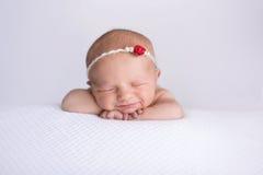Att le som är nyfött, behandla som ett barn flickan som bär en röda Rose Headband Royaltyfri Foto