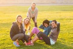 Att le sportiga kvinnor som att göra sitter, ups under konditiongrupp Arkivbilder