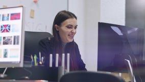 Att le stilfull brunett arbetar på en dator modern kontorskvinna för affär lager videofilmer