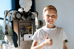 Att le ungevisning tummar upp den near mänskliga roboten Arkivfoto