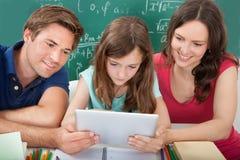 Att le uppfostrar att hjälpa dottern, i att använda den digitala minnestavlan Arkivbild