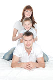 Att le uppfostrar med lite sonen som ligger på vitbakgrund Royaltyfri Foto