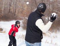 Att leka för familj kastar snöboll arkivfoto