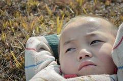 Att lägga det asiatiska lantliga barnet är att tänka Arkivfoto