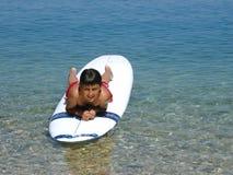 att ligga för strandpojke surfar Royaltyfri Bild