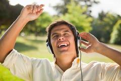 Att lyfta för man som är hans, beväpnar stunder genom att använda hörlurar för att sjunga along till musen Royaltyfria Foton