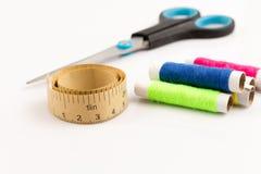 Att mäta bandet med rullen och scissor på vit Fotografering för Bildbyråer