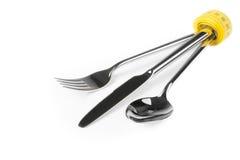Att mäta den near skeden för bandet, kniven och gaffeln, begrepp av näring och bantar Royaltyfria Bilder
