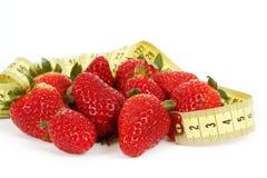 Att mäta tejpar runt om en jordgubbe som ett symbol av bantar Royaltyfri Fotografi