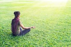 Att meditera för yogakvinna som är utomhus- parkerar in, på bakgrund för gräsfält royaltyfri fotografi